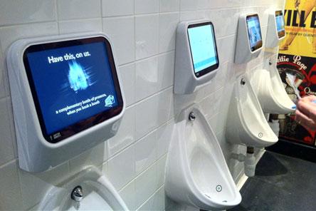 Реклама на экранах мониторов над писсуарами