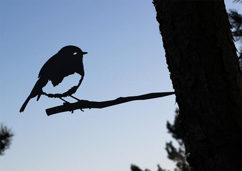 Стальная птица на ветке дерева